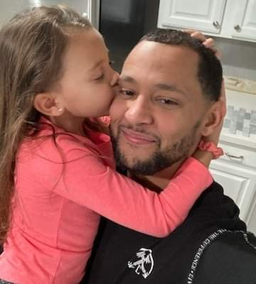 A photo of a smiling Nate with his daughter, and her arms are wrapped around his neck while she kisses him on the cheek.