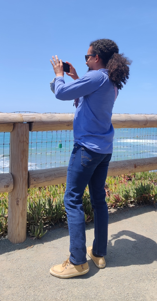 A picture of Ben standing on a lookout point of Moonstone Beach in Cambria, California, filming the view.